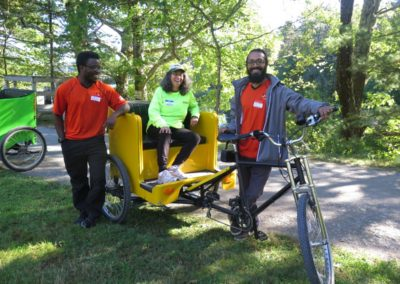 WooRides pedicab bike with two drivers and a passenger ready to go