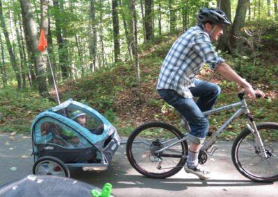 Man riding bike pulling children in kiddie trailer