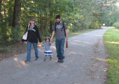 Couple walking with small child on rail trail
